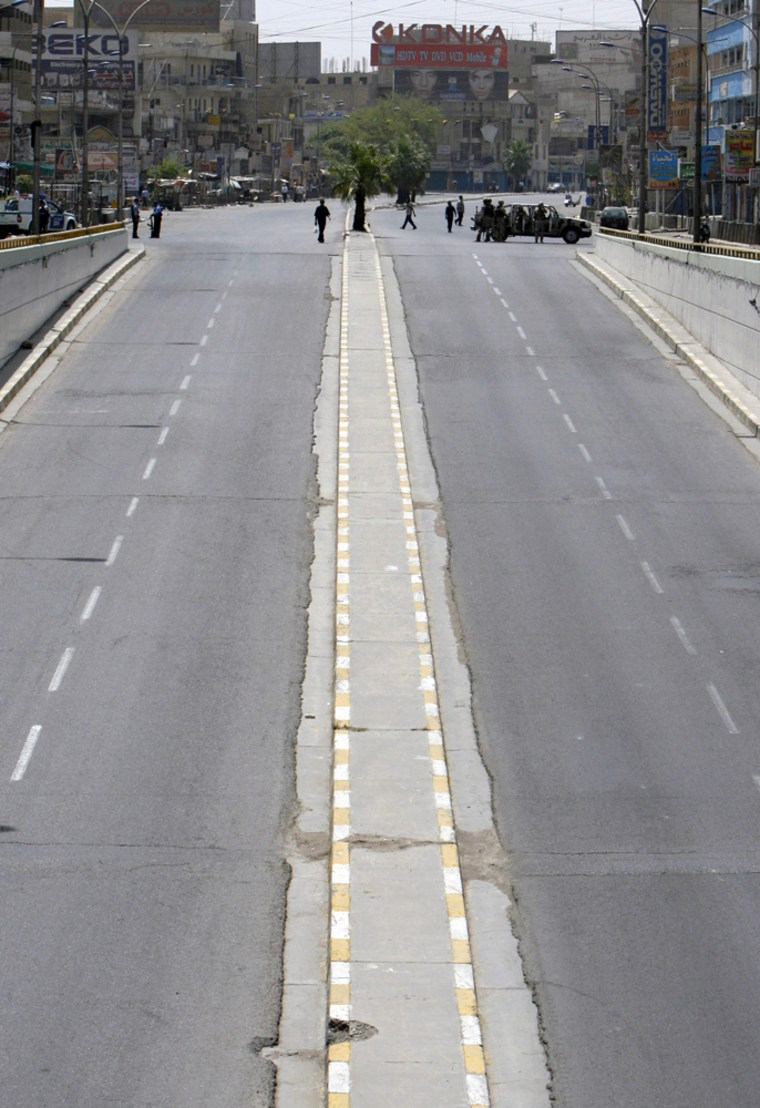 Police set up checkpoint on empty road as Iraqi authorities enforced traffic ban in Baghdad