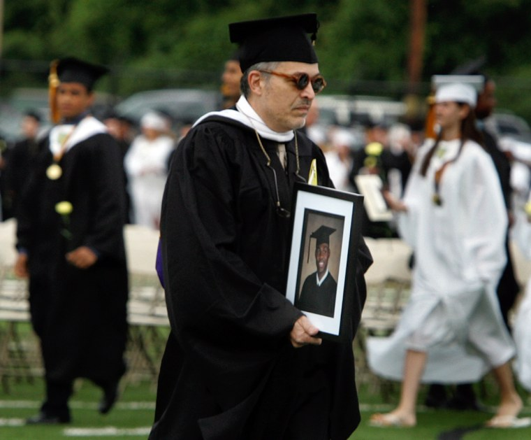 Harry S. Truman High School theater teacher Lou Volpe carries a photograph of Tyrone Lewis to an empty seat during graduation ceremonies in Bristol Township, Pa., on Friday.