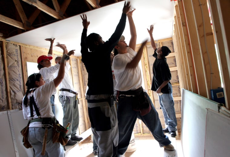 Amanda Phillips, left, Habitat site supervisor, and Shelly Morrison, Manager of the Cardozo Construction and Design Academy, in red hat, direct student-volunteer workers as they install sheetrock in a new Habitat property off of Blaine Street, in Washington D.C.