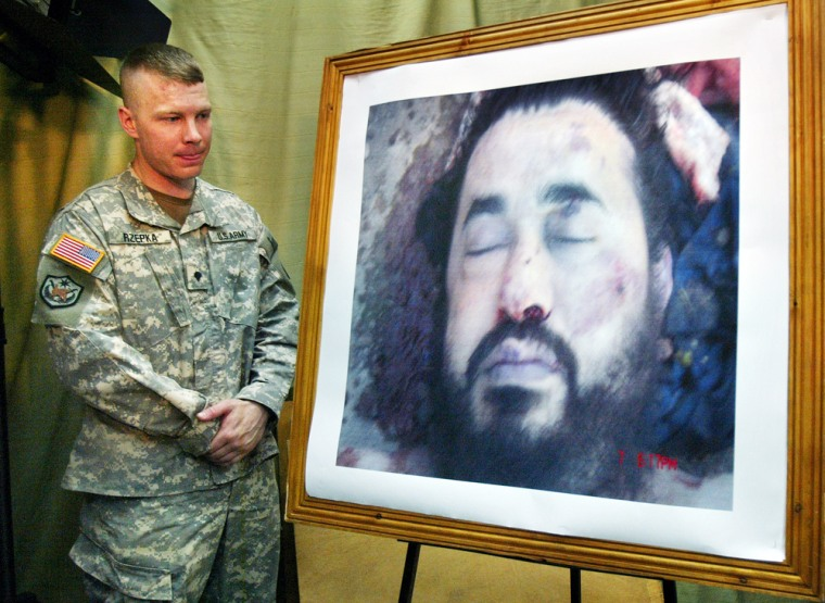 A U.S. soldier at a press conference in Baghdad on Thursday stands guard next to a photo purporting to show the body of Abu Musab al-Zarqawi, the al-Qaida-linked militant who led a bloody campaign of suicide bombings, kidnappings and hostage beheadings in Iraq, who was killed Wednesday night in a U.S. airstrike.