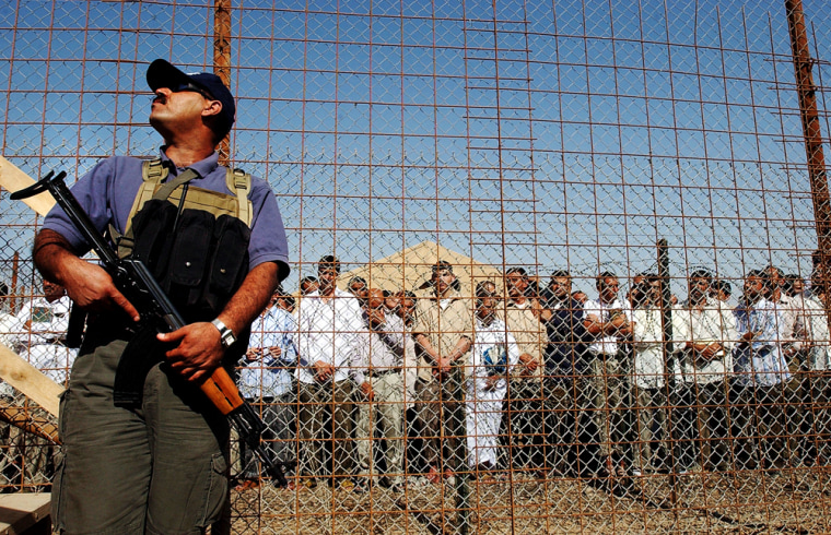 Iraqi prisoners wait to be released on Sunday as a security guard stands guard at Abu Ghraib prison, west of Baghdad.