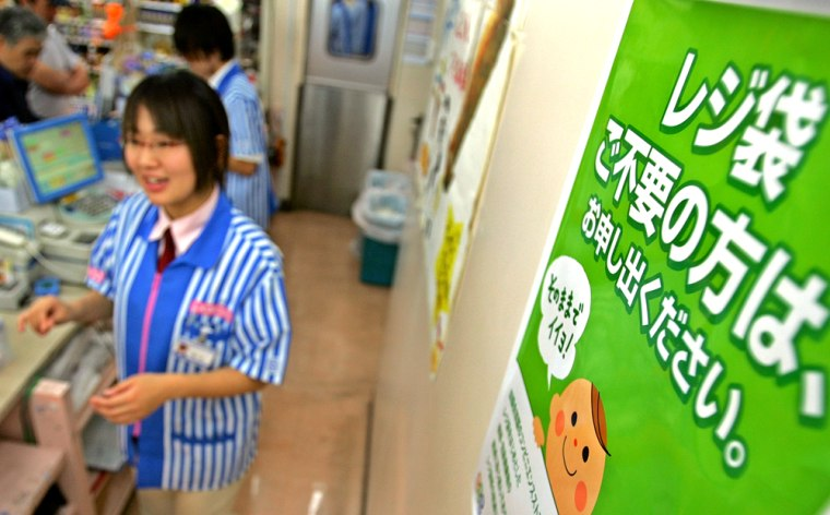"""Clerks at a Tokyo convenience store work near a poster that reads: """"Please mention if there's no need for plastic bags."""""""