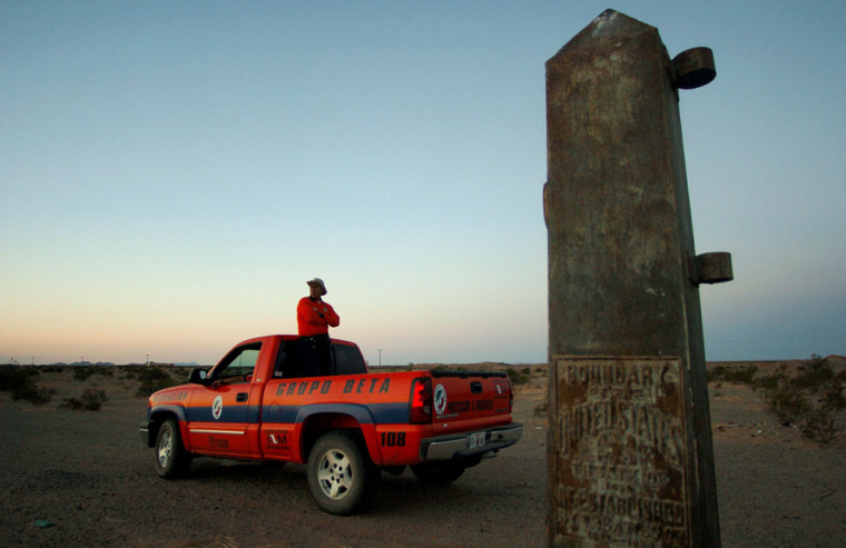 Carlos Estrada, a police agent working with the Mexican government's migrant assistance unit, stands in the back of a pickup truck next to an international boundary marker on Thursday in the desert near San Luis Rio Colorado, Mexico.