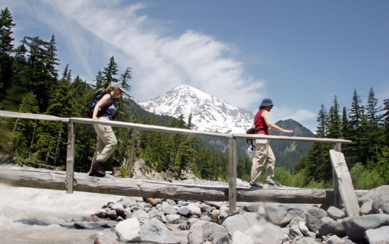 Two hikers cross a bridge over the Nisqually River under the shadow of Mount Rainier in Mount Rainier National Park.