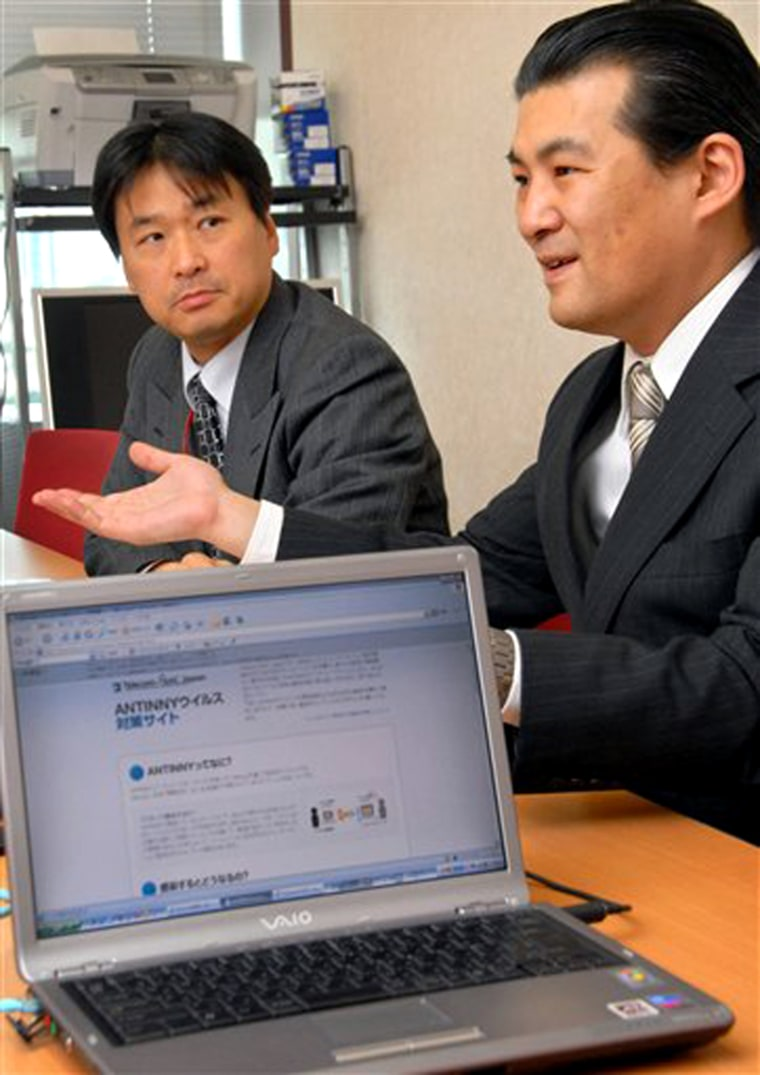 Mamoru Saito, right, of Telecom Information Sharing and Analysis Center Japan, speaks to The Associated Press as his laptop displays counter measures of computer virus, Antinny.