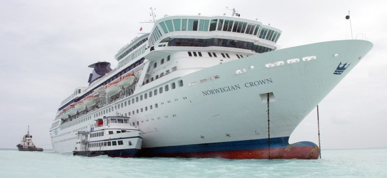A small ferry tender takes passengers off the Norwegian Crown cruise ship while tugboats keep the vessel in place after it ran aground off Hamilton, Bermuda. No one was hurt.
