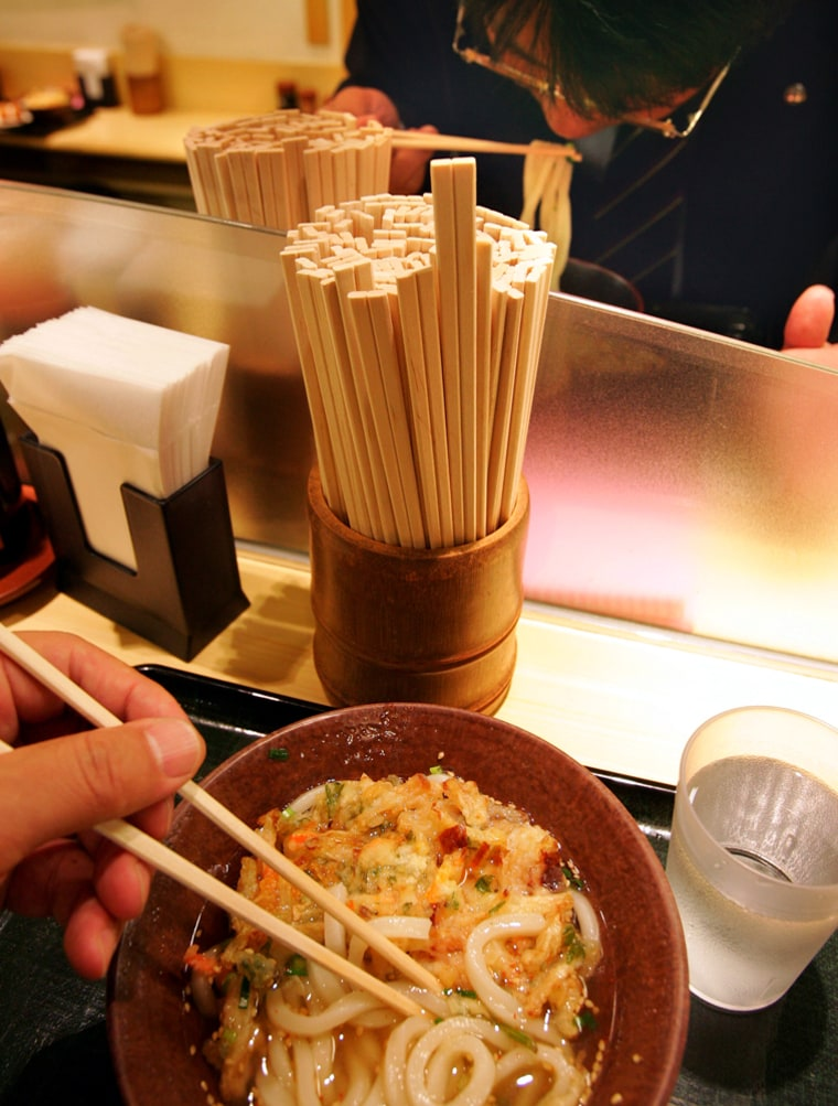 People eat noodles using chopsticks called 'waribashi' at a fast-food chain restaurant in Tokyo.