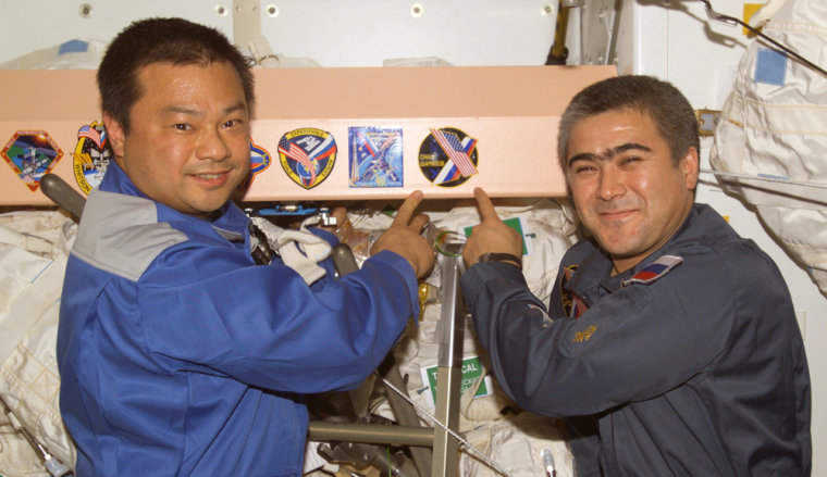 NASA's Leroy Chiao and Russian cosmonaut Salizhan Sharipov point to a patch for their mission on the international space station, Expedition 10, after their arrival in October 2004. Their purported signatures appeared on Confederate flags that were offered for sale — but the seller later said he withdrew the items because he had concluded they were forgeries.