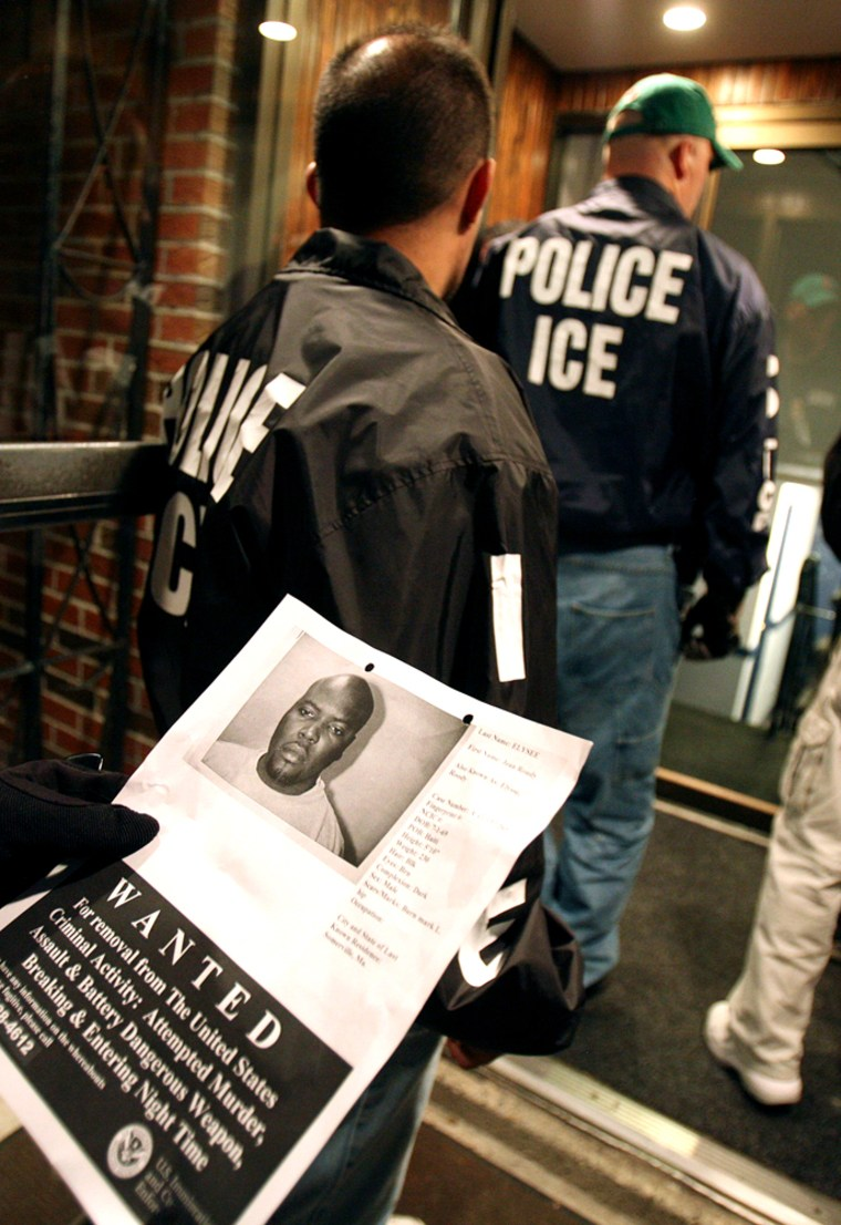 Members of an Immigration and Customs Enforcement task force enter an apartment building during a sweep to capture fugitiveillegal aliens onWednesday in Everett, Mass.