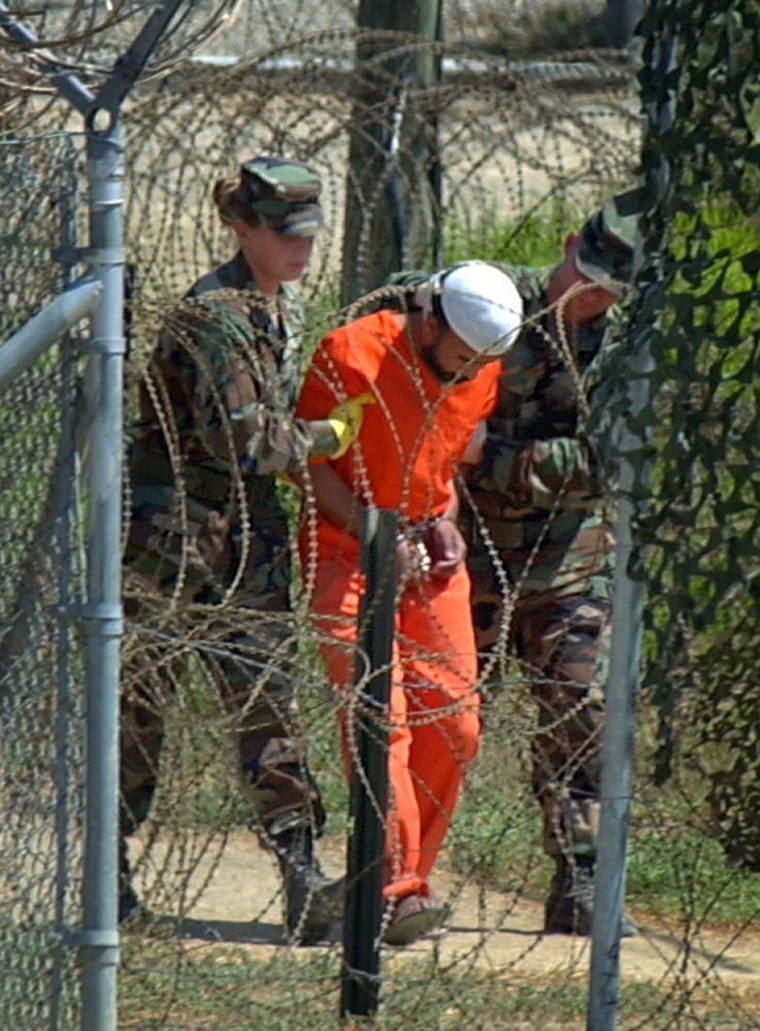 A Camp X-Ray detainee is escorted to interrogation by U.S. military guards at the Guantanamo Bay U.S. Naval Base, Cuba, in February 2002.