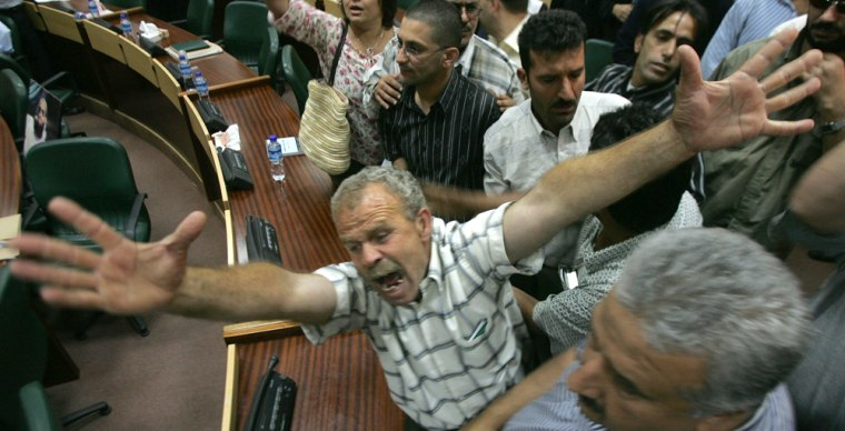 The Palestinian parliament in Ramallah erupted into chaos on Wednesday as dozens of civil servants demanded long-overdue salaries, attacked Hamas lawmakers and forced the parliament speaker to flee the building.