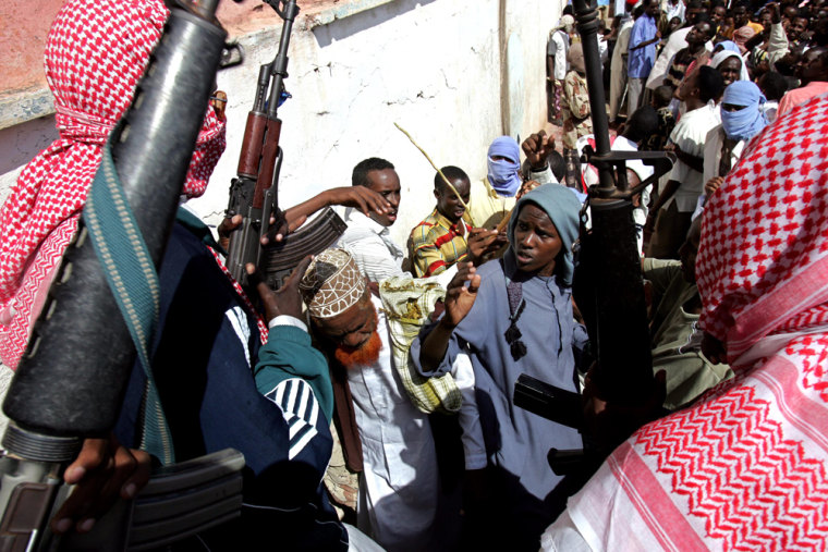 Militia from the Islamic Courts Union control a crowd in Mogadishu on Friday during a demonstration against a peacekeeping proposal that would bring foreign troops into the country.