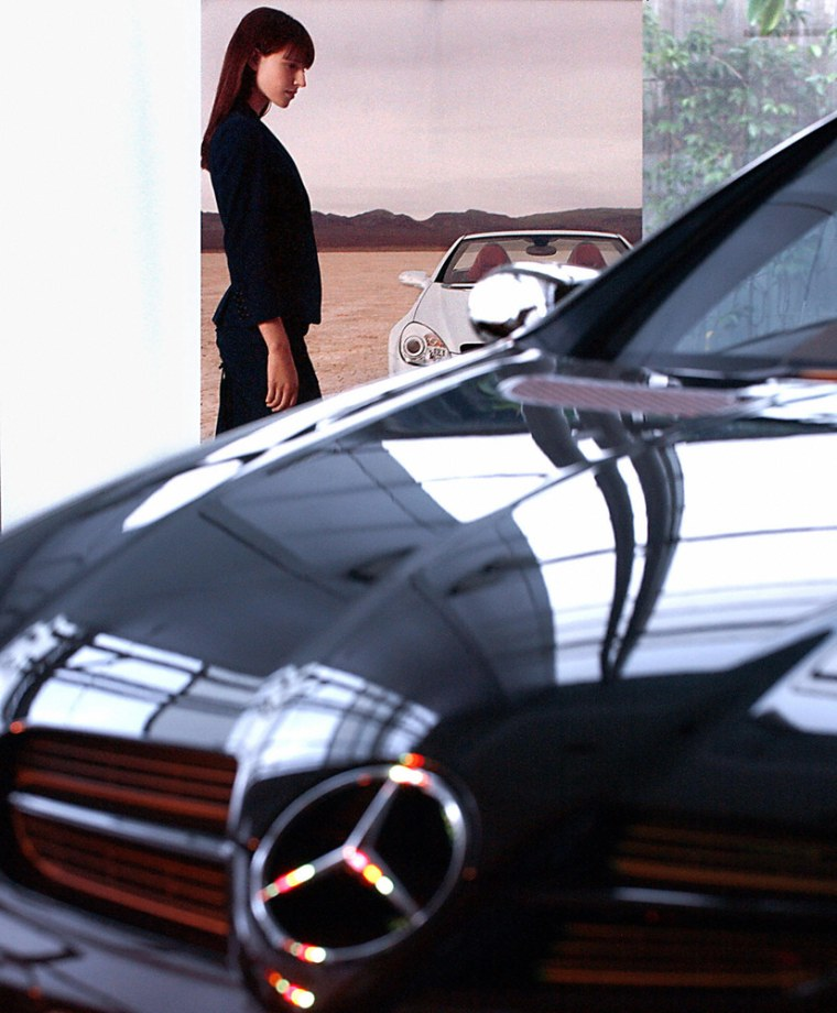 Models pose with a Mercedes Benz SLK 200
