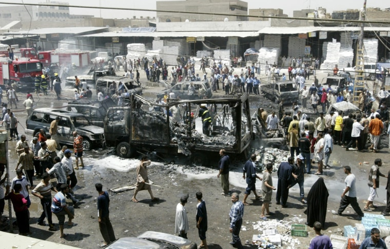 Residents gather at the scene of a car bomb attack in a crowded market in Baghdad
