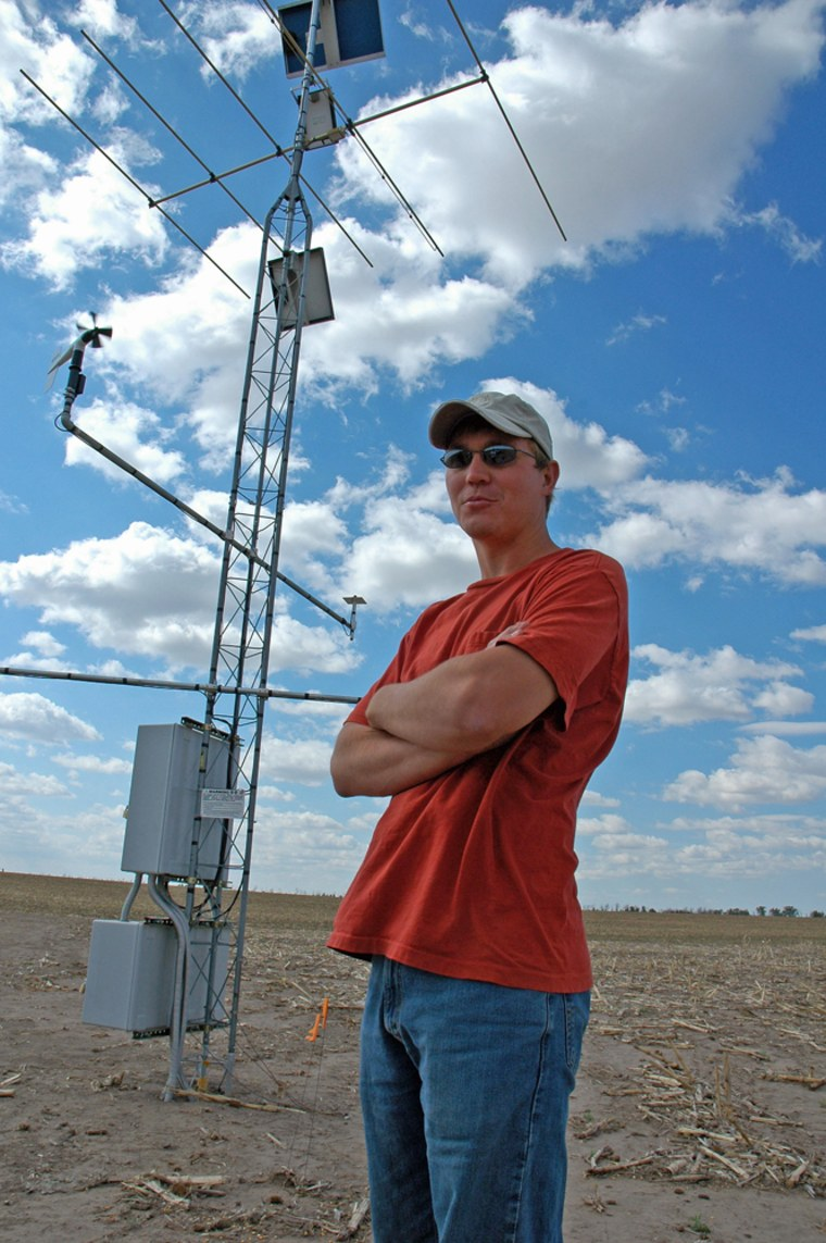 Curtis Johnson, whose family farm outside Imperial, Neb., is enrolled in a test of the potential for ethanol production using corn stalks and similar material, stands in front of a weather station that is part of the scientific study.