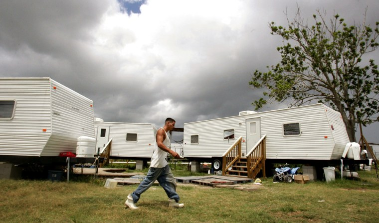 Shrimp boat deck-hand Gilhang walks past neighbors' FEMA trailers after taking break from work in Venice, Louisiana