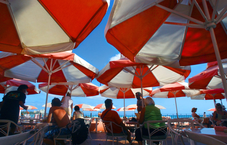 Colorful umbrellas block out the sun for visitors to the beachside Mai Tai Bar at the popular Royal Hawaiian Hotel on Waikiki Beach in Honolulu, Hawaii.
