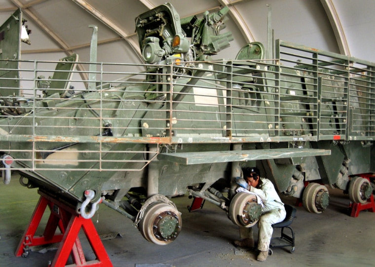 A military contractor inspectsa U.S. Army Stryker transport vehicle at Camp Anaconda in Balad, Iraq, on Saturday.