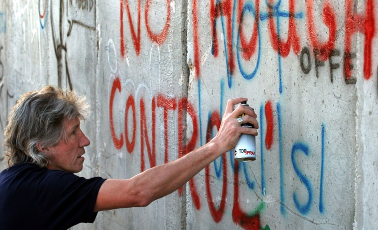 """British rock musician and Pink Floyd co-founder Roger Waters spray-paints the words """"No Thought Control"""" on a section of Israel's separation barrier in the West Bank Wednesday. Waters wrote slogans on the wall in protest against the construction of the barrier, which Palestinians say is a land grab and Israel says is necessary for its security."""