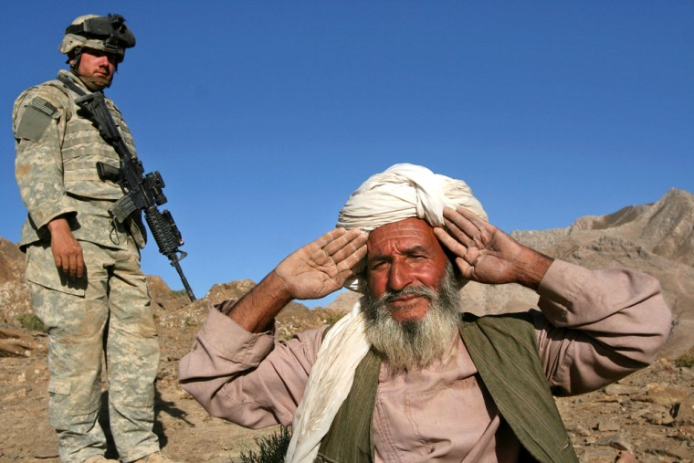An Afghan villager holds his hands up to show he has no weapons before being searched by U.S. Army Staff Sgt. Mathew Banaszewski at Helmand Province, Afghanistan, on Wednesday.