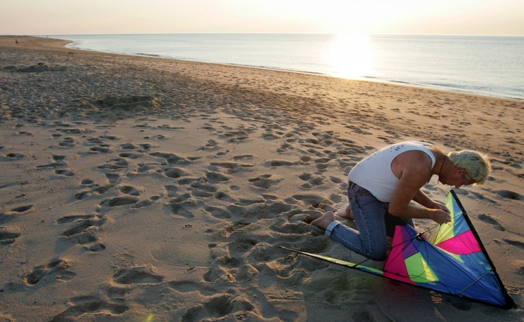 A manprepares his kite for flight just before sunset on the beach at the Cape Cod National Seashore.