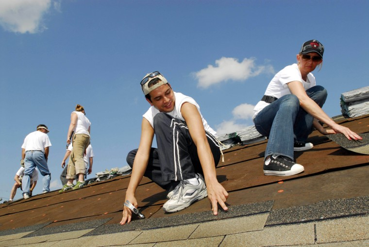 Hard Rock Cafe employees Omar Nunez, center,and Annie Balliro, right, help with a Habitat for Humanity project at the Musicians Village in New Orleans, May 24, 2006.