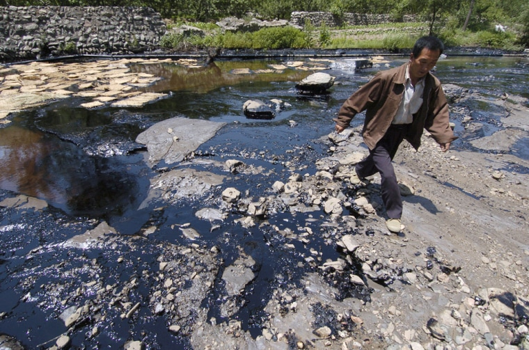 Avillager walks past a spill of toxic coal tar in the Dasha River in China's northern Shanxi province. The spill of 60 tons of coal tar into the river was the latest in a series of mishaps to degrade the country's already polluted waterways.