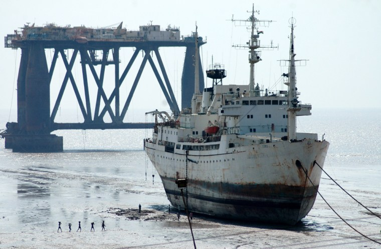 Workers walk past a ship and an oil drilling rig, both waiting to be dismantled at a ship breaking yard in Alang, in the western India. After spending 20 to 30 years on the high seas, ships some as tall as 15-story buildings and as long as several football fields, make their way to beaches across India andBangladesh to be dismantled.