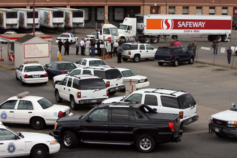 Police vehicles block the entrance to a Safeway distribution center in Denver after Sunday's shooting.