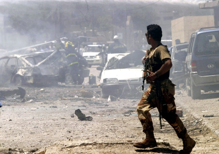 A soldier rushes to a petrol station shortly after a car bomb exploded which killed three people and wounded 21 others in Kirkuk