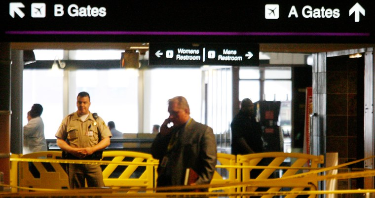 Police investigatethe scene of Tuesday's shooting at McCarran International Airport in Las Vegas.