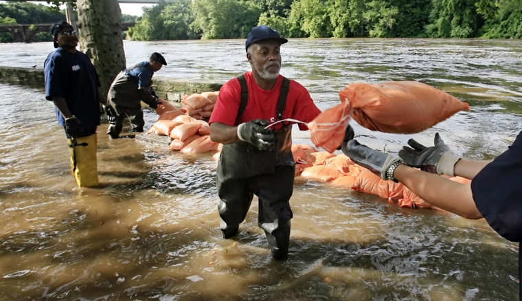 As water rises above the banks of the Schuylkill River, Philadelphia Water Department workers remove submerged sandbags to reuse and protect a firehouse and nearby homes.
