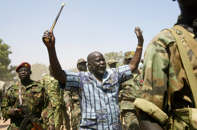 John Garang, then leader of the Sudan People's Liberation Army, is surrounded by soldiers as he waves at the crowd in a January 2005 file photo in southern Sudan. From Africa to Indonesia, the number of wars worldwide has dropped to a new low, peace researchers report. But they say the face of conflict is changing.