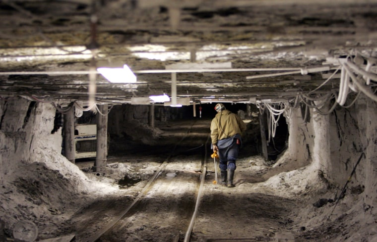 A worker in an Alabama coal mine walks beside a rail car track. American mining operations of all types are experiencing shortages of equipment and workers.