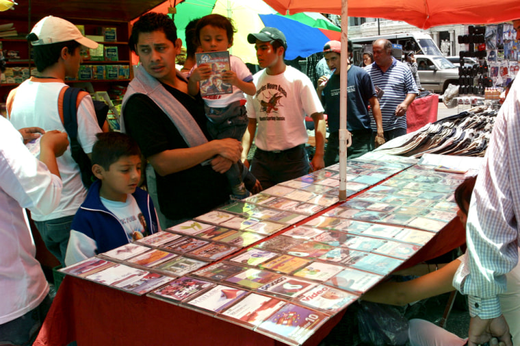 People shop for pirated music CDs in downtown Mexico City, Mexico on June 27, 2006. The pirate albums sell for 20 pesos, just under $2 apiece, about one-tenth of the in-store price.