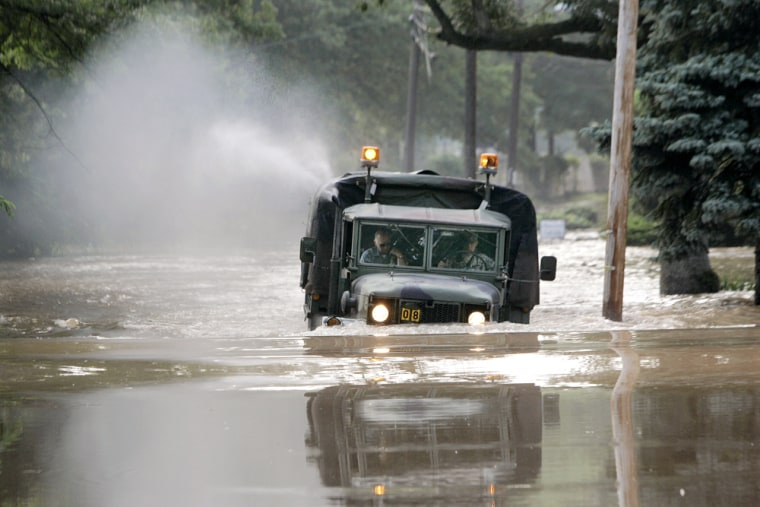 A truck borrowed from a military academy in Trenton, N.J., searches for stranded residents Thursday. Thousands of people along the Delaware River fled their homes.