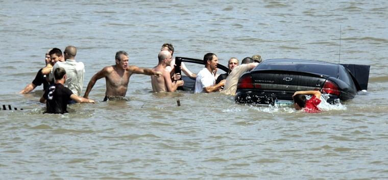 People gather Sunday around a car that ran into the Ohio River in Madison, Ind., during the Madison Regatta, an annual Fourth of July event. The car plowed through the crowd first,injuring several spectators.