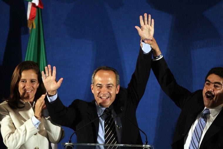 Presidential candidate Felipe Calderon raises his hand in Mexico City