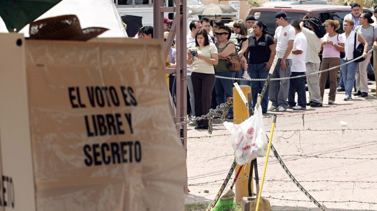 Voter casts his ballot while others wait in line at polling station during Mexico's presidential election in Nogales