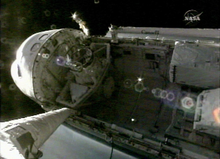 Space Shuttle Discovery's docking port can be seen inside the payload bay of the orbiter in this view from a video camera