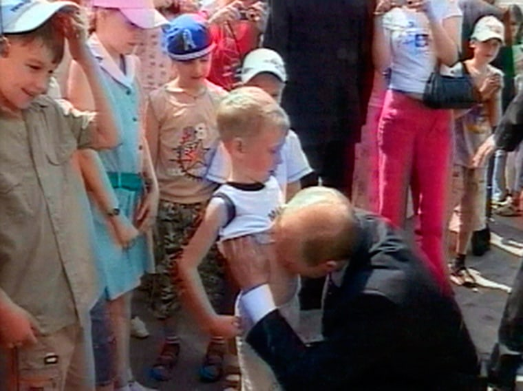 Russian President Vladimir Putin lifts the shirt of a young boy named Nikita and kisses his stomachJune 28 at the Kremlin in Moscow, in this image taken from Russian state television.