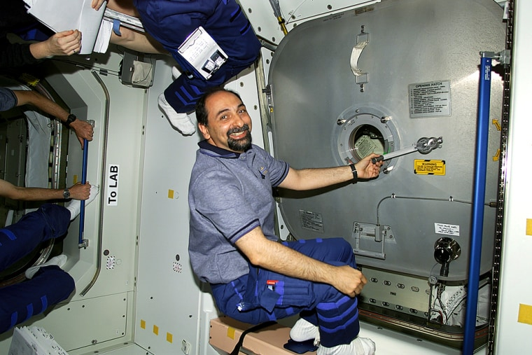 Italian astronaut Umberto Guidoni hangs onto a door handle at one of the international space station's hatches during a shuttle mission in 2001.