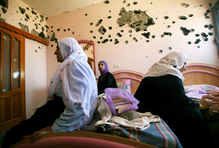 Palestinians from the Al Aljuwi family sit in their house next to a wall riddled by Israeli army gunfire after the army pulled back from Beit Lahiya, northern Gaza Strip, on Saturday.