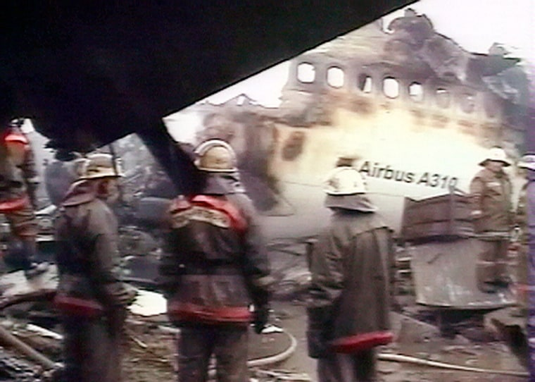 Firefighters work at the smoldering wreckage of an Airbus A-310 plane in the Siberian city of Irkutsk early Sunday in this image from television.