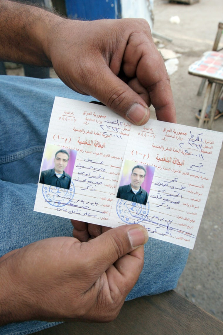 An Iraqi in Baghdad on Monday displays two ID cards he made for the same person; one ID bears a Sunni name, one with a Shiite name.
