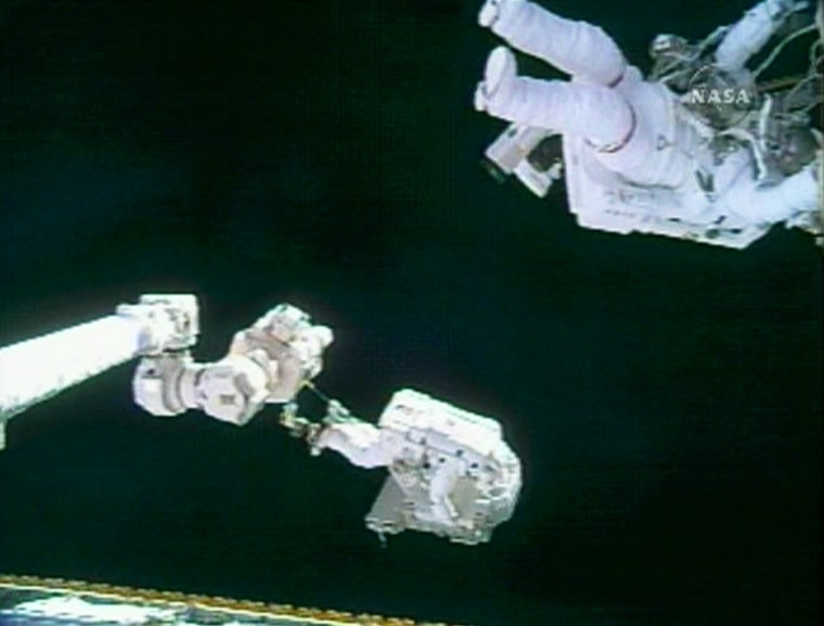 In the lower part of this picture, spacewalker Mike Fossum can be seen carrying a 330-pound cable reel system while attached to the shuttle Discovery's robotic arm. Meanwhile, at upper right, crewmate Piers Sellers makes his way along the international space station's hull hand over hand.