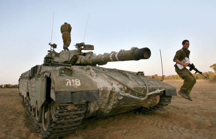 An Israeli soldier jumps from a tank on the field in Kissufim area