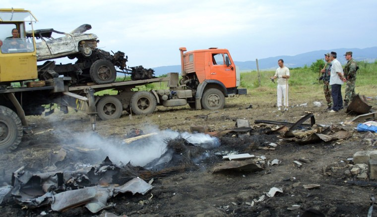 Police officerssurvey the wreckage of a truck and cars blown up where Chechen warlord Shamil Basayev and other rebels were killed Monday in a special operation in the Ingush village of Ekazhevo.