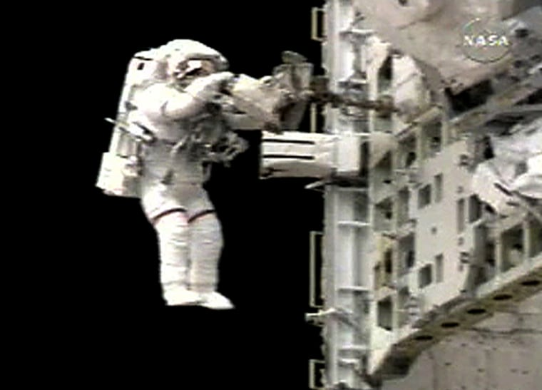Spacewalker Sellers puts away tools on the tool pallet in the Shuttle Discovery's payload bay near the end of the EVA
