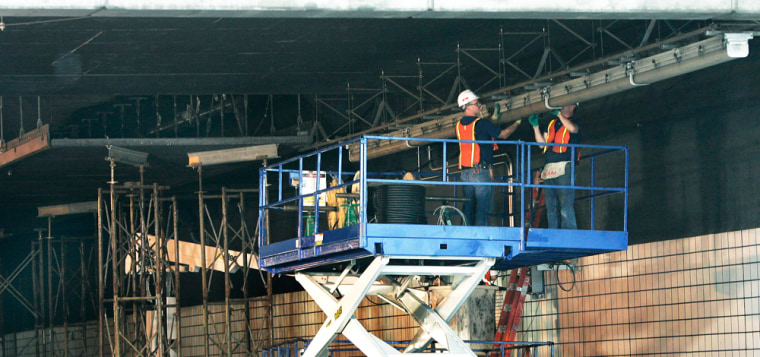 Men work inside the I-90 tunnel in Boston onWednesday near where 12 tons of concrete ceiling panels fell late Monday night, crushing a passing car and killing a woman.